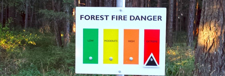 sign in forest with arrow indicating fire rating is extreme