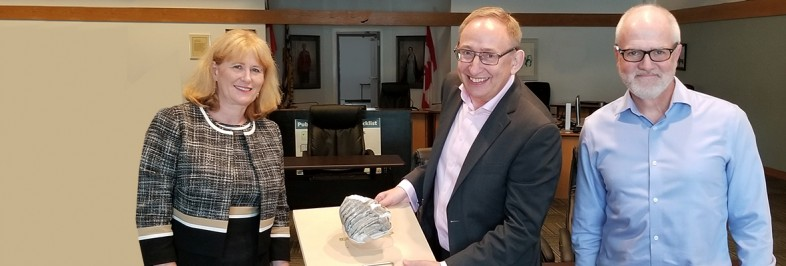 Royal BC Museum CEO and Deputy CEO holding the mammoth tooth