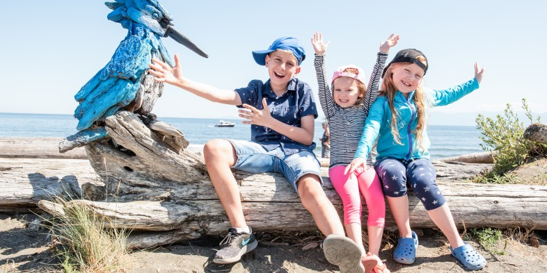 kids with driftwood art at the beach