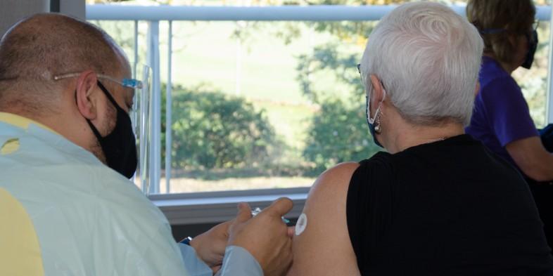 pharmacist administering flu vaccine to elderly woman