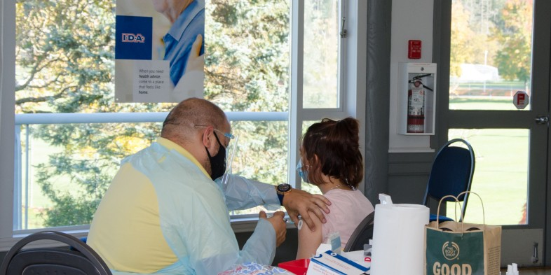 pharmacist administering flu vaccine to young girl