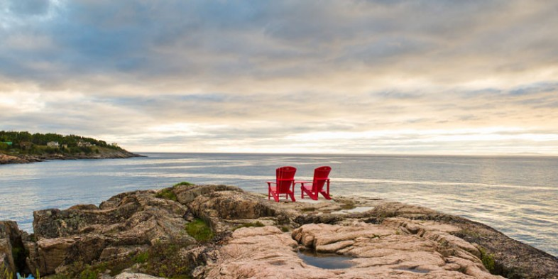 parks canada red adirondak chairs on the rocks overlooking the ocean