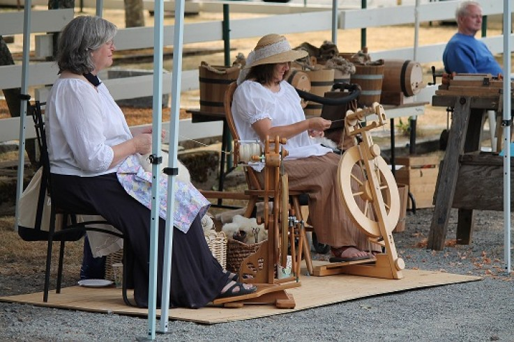 The ladies peacefully spin their wool.