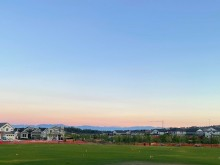 meadow park green at twilight surrounded by homes with the mountains in the distance